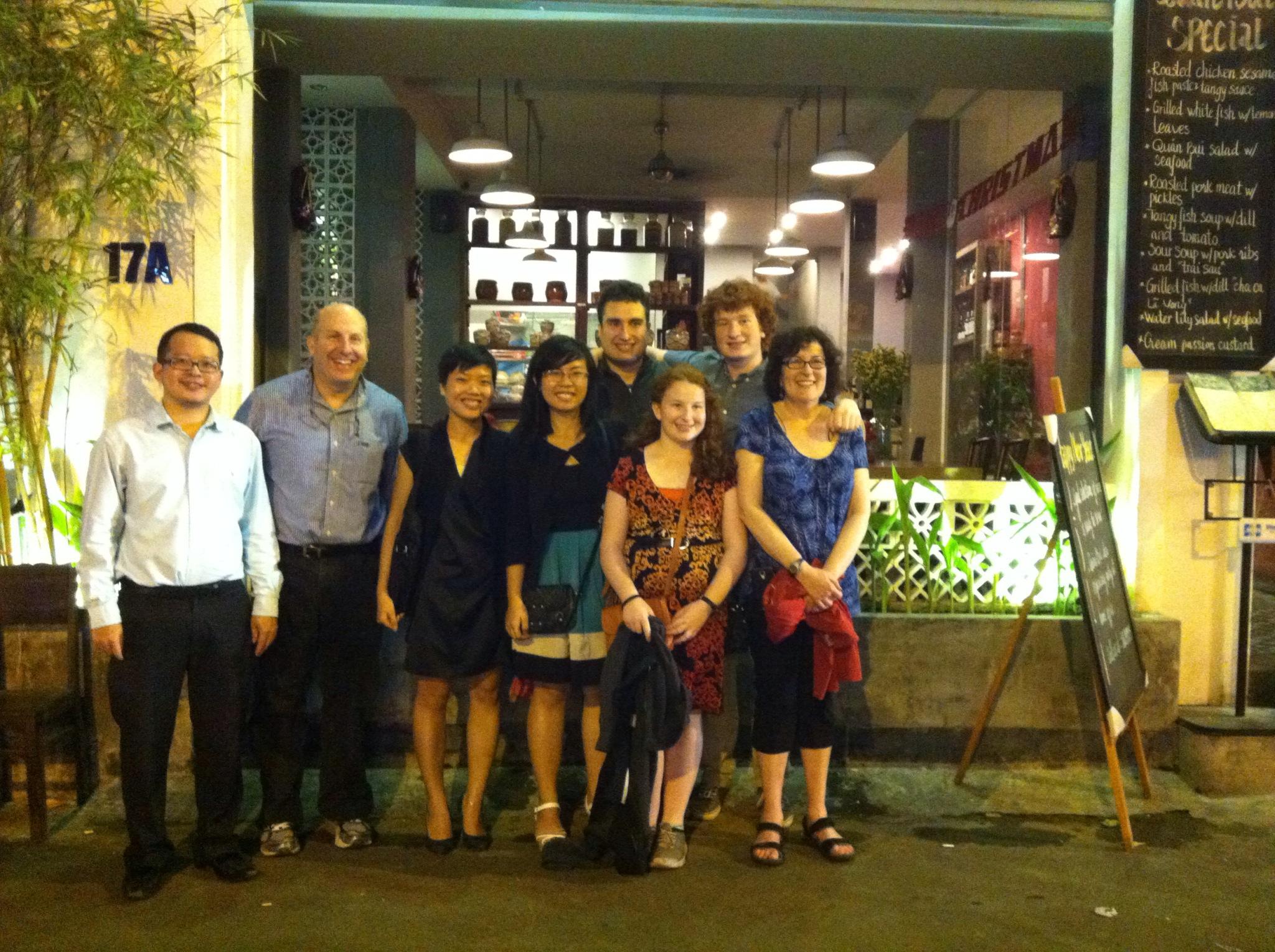 A group including President Krislov outside a restaurant