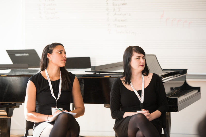 Kelsey Scult  and Mary Okoth are seated by a grand piano, paying attention to a speaker outside the frame.